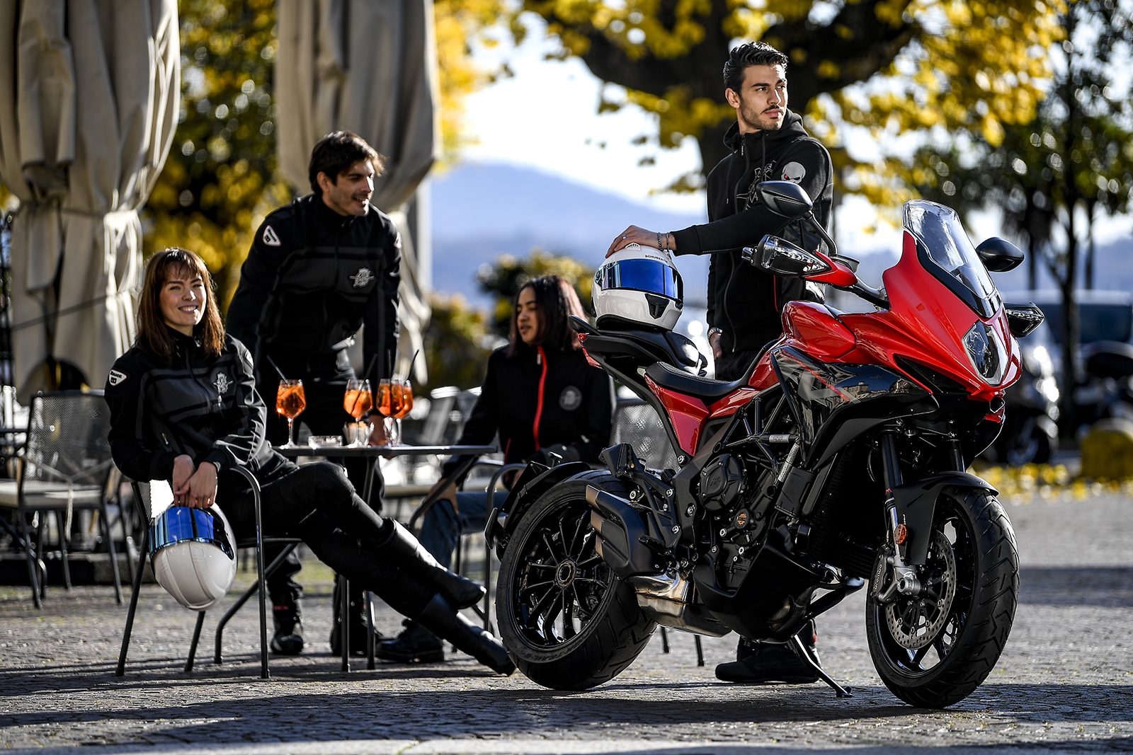 four riders drinking aperol spritz in Italy, with a red turismo veloce on its side stand, and apart of the new mv agusta rosso range