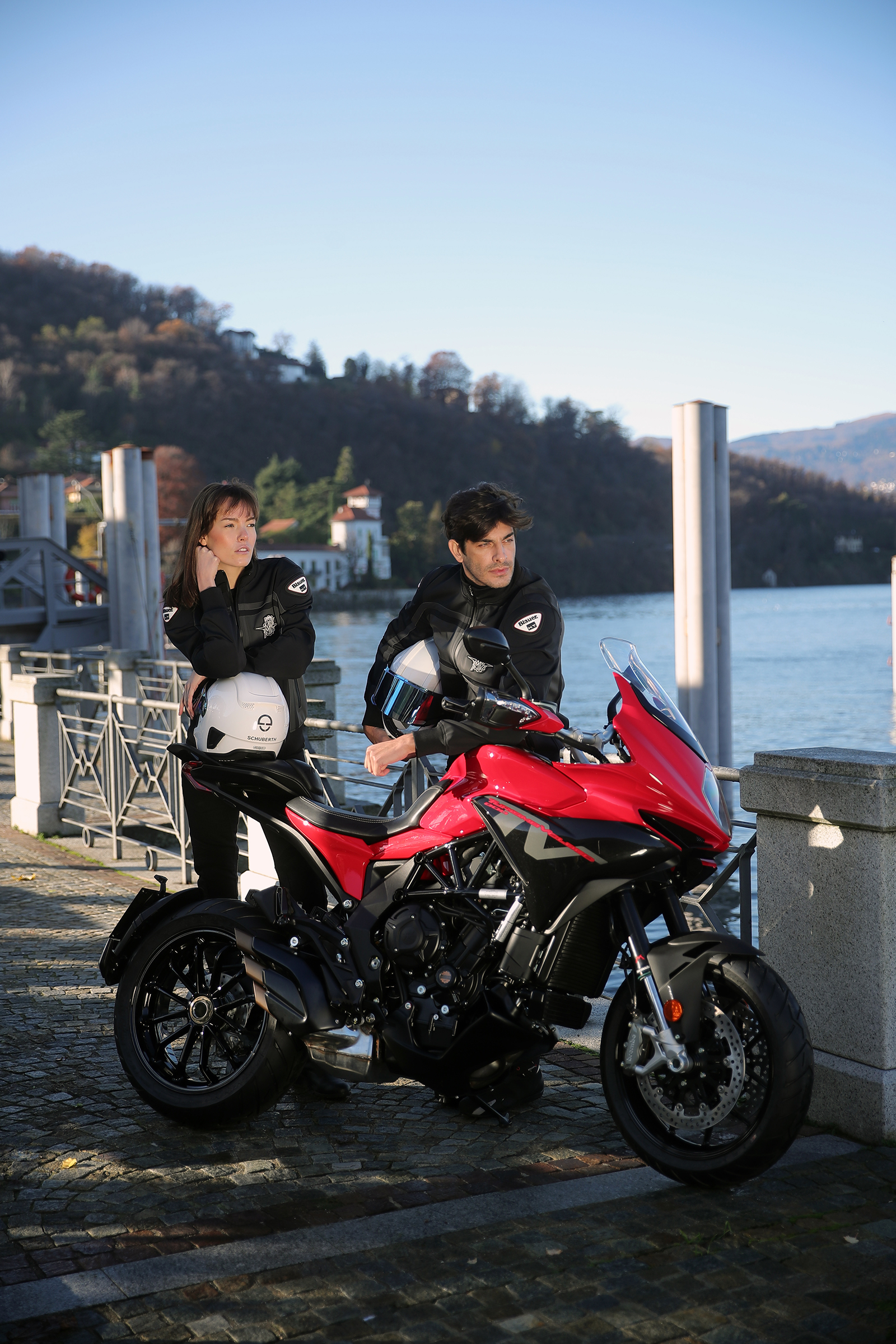 turismo veloce rosso parked near the waters edge with a male and female rider holding their helmets